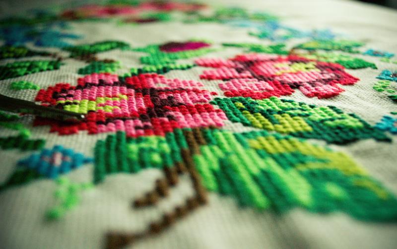 """""""A SÁRRÉT VIRÁGAI A LAKÁSTEXTILEKEN"""" CÍMŰ KIÁLLÍTÁS: Illusztratív fotó egy élénk zöld és rózsaszín színeket használó, virágot ábrázoló textilhímzésről"""